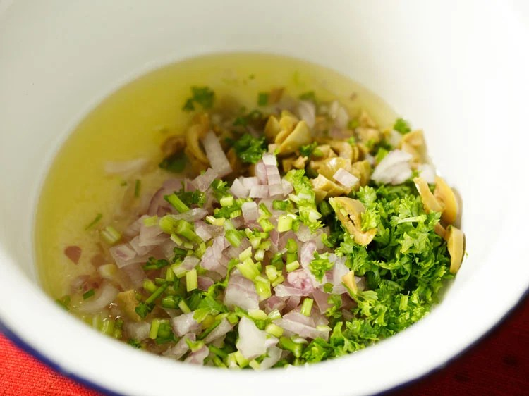chopped onions, olives, celery and parsley added into the bowl for mayo dressing