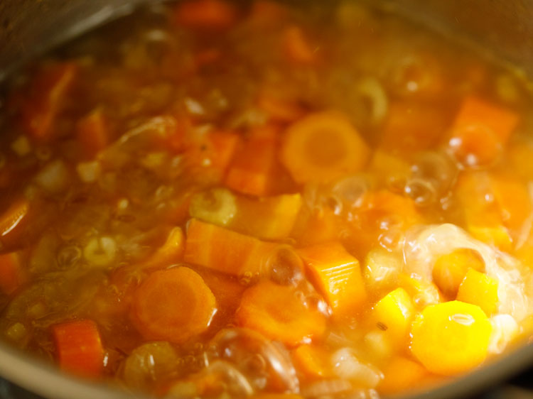 checking carrot soup mixture while simmering