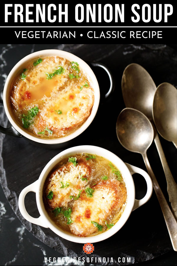 french onion soup in two cream colored soup bowls with spoons on a black slate tray. soup garnished with some parsley.