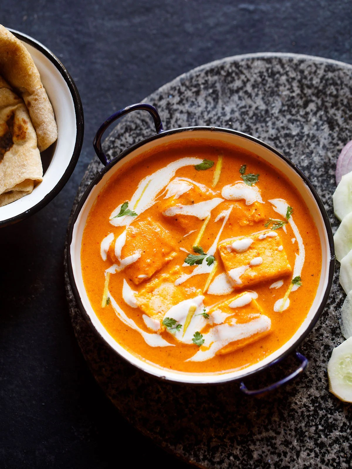 paneer butter masala served in a blue rimmed white pan, garnished with cream and cilantro with a side of sliced cucumber and roti