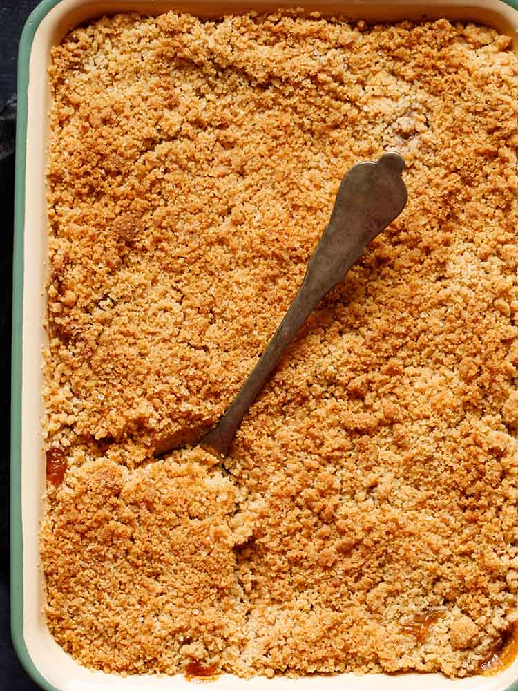 top shot of apple crumble in the baking tray with a brass serving spoon inside on lower left hand side of the crumble