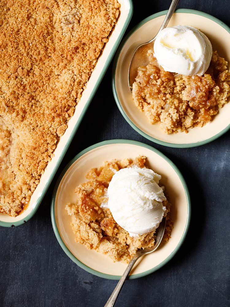 apple crumble topped with a scoop of vanilla icecream in a green rimmed cream plate with a dessert spoon