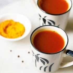 Turmeric Tea served in off white small cups with a black flower design on the cup. Cups placed on a white marble board with a small bowl or turmeric and a few black pepper thrown on the marble board