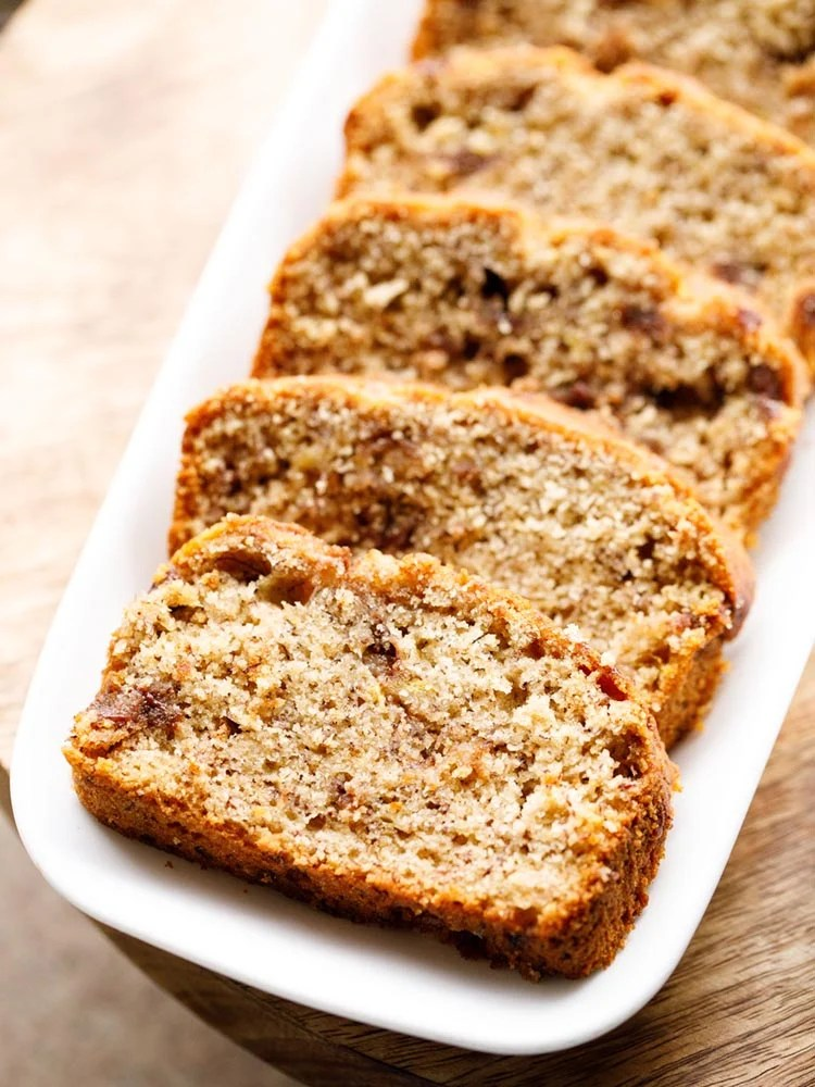 Chocolate Chip Banana Bread slices kept on a white rectangular tray on a wooden board
