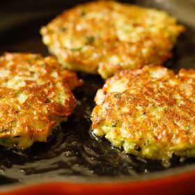 zucchini fritters turned over when one side is golden and crisp