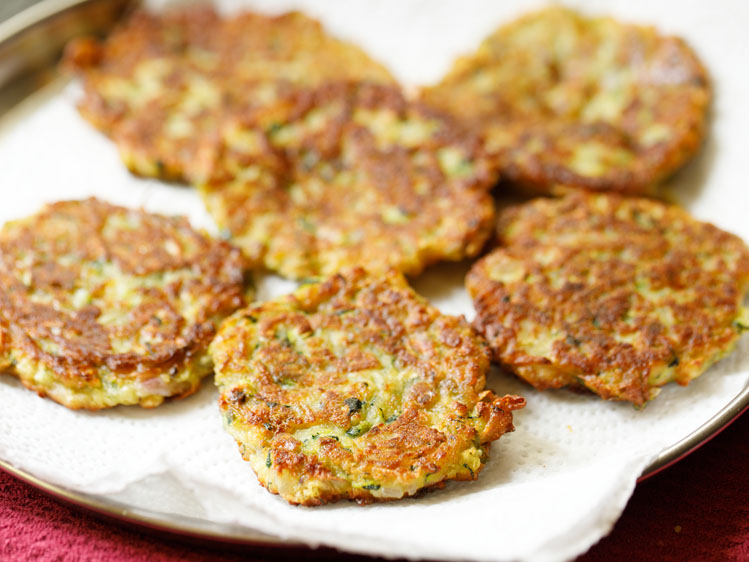 fried crispy zucchini fritters kept in kitchen paper towels