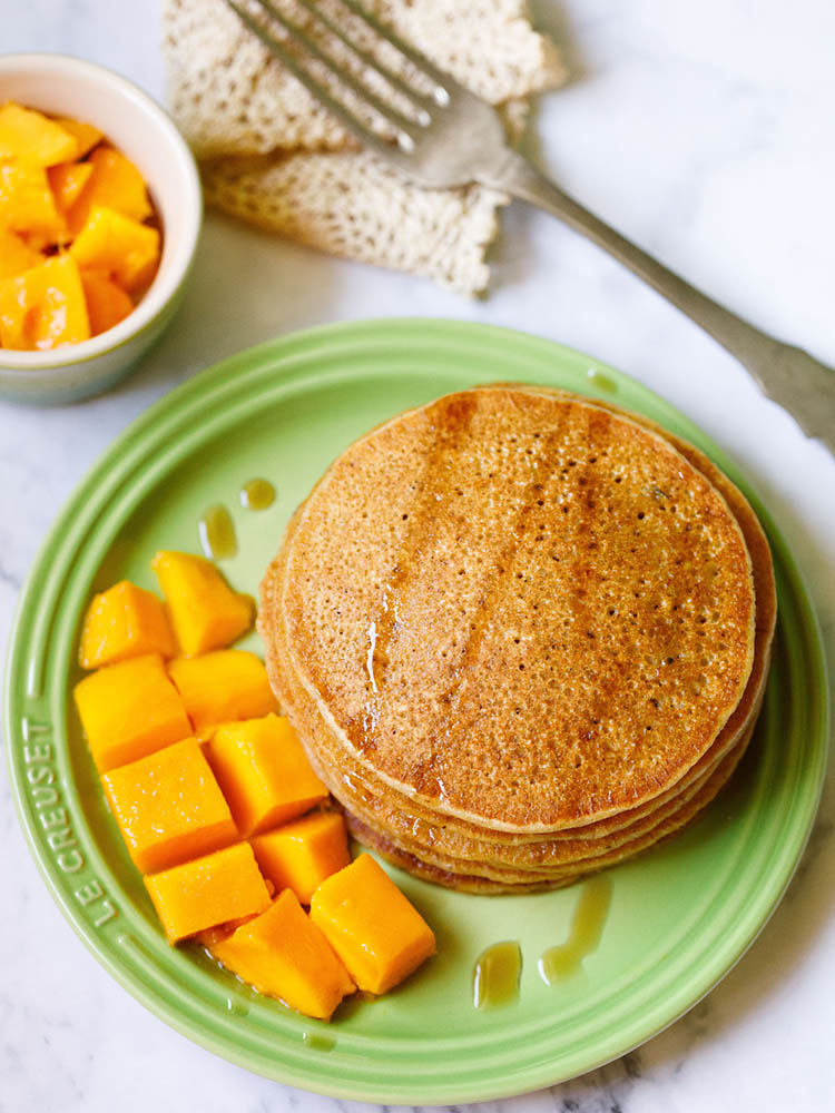 pumpkin pancakes stacked on green plate drizzled with maple syrup with a side of cubed mangoes, a small bowl of mangoes on top right and with a fork kept on folded crochet doily near top left on a white marble background