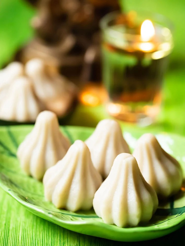 ukadiche modak placed on a green leaf shaped platter on a green colored board