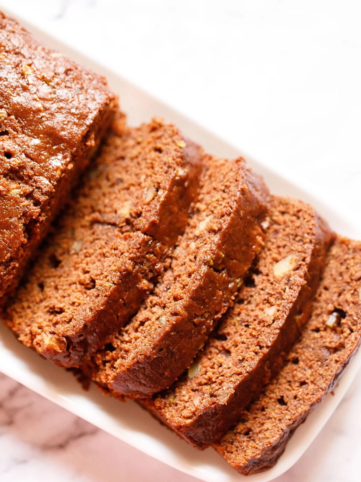 chocolate zucchini bread sliced in four slices and the entire loaf and the slices are kept on a white rectangular tray on a white marble background