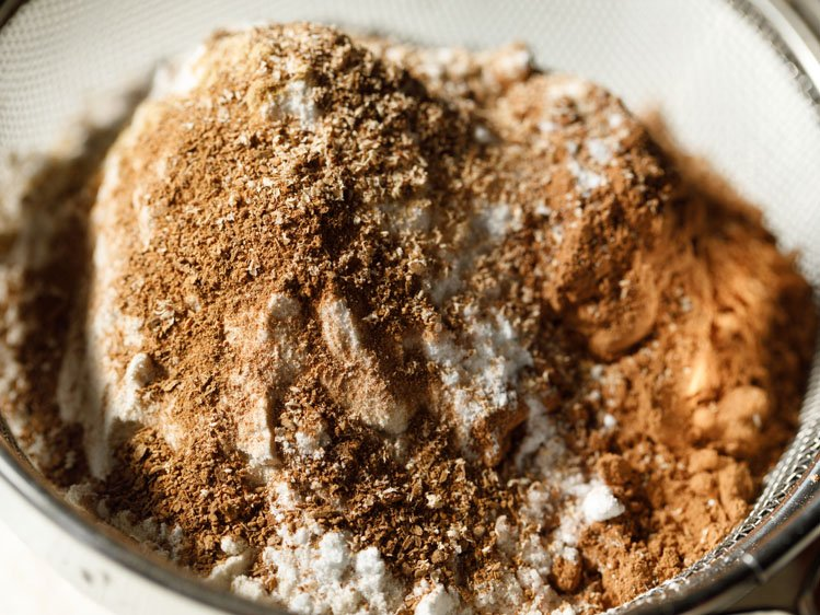 spice powders added to whole wheat flour and cocoa powder in a sieve