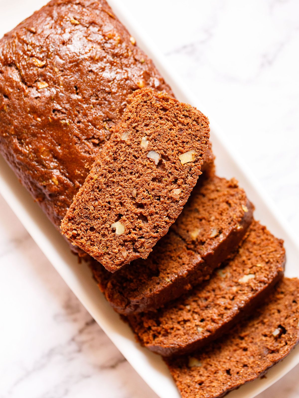 zucchini bread partly sliced with one slice kept on top of the loaf on a white rectangular tray on a white marble background