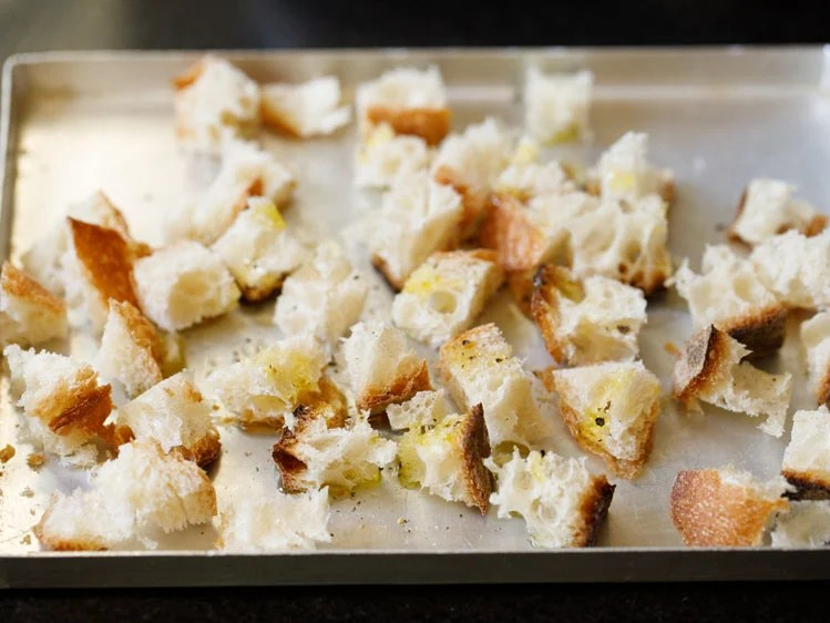 cubed bread drizzled with olive oil and crushed black pepper in a metal baking tray