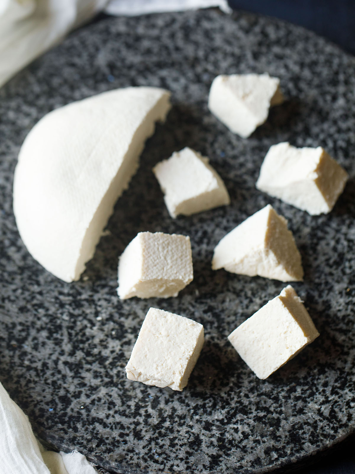 paneer cheese halved and cut in cubes on a grey-black granite round board