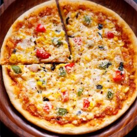 Whole round Pizza on a wooden pizza plate with a cut triangular slice on left top side