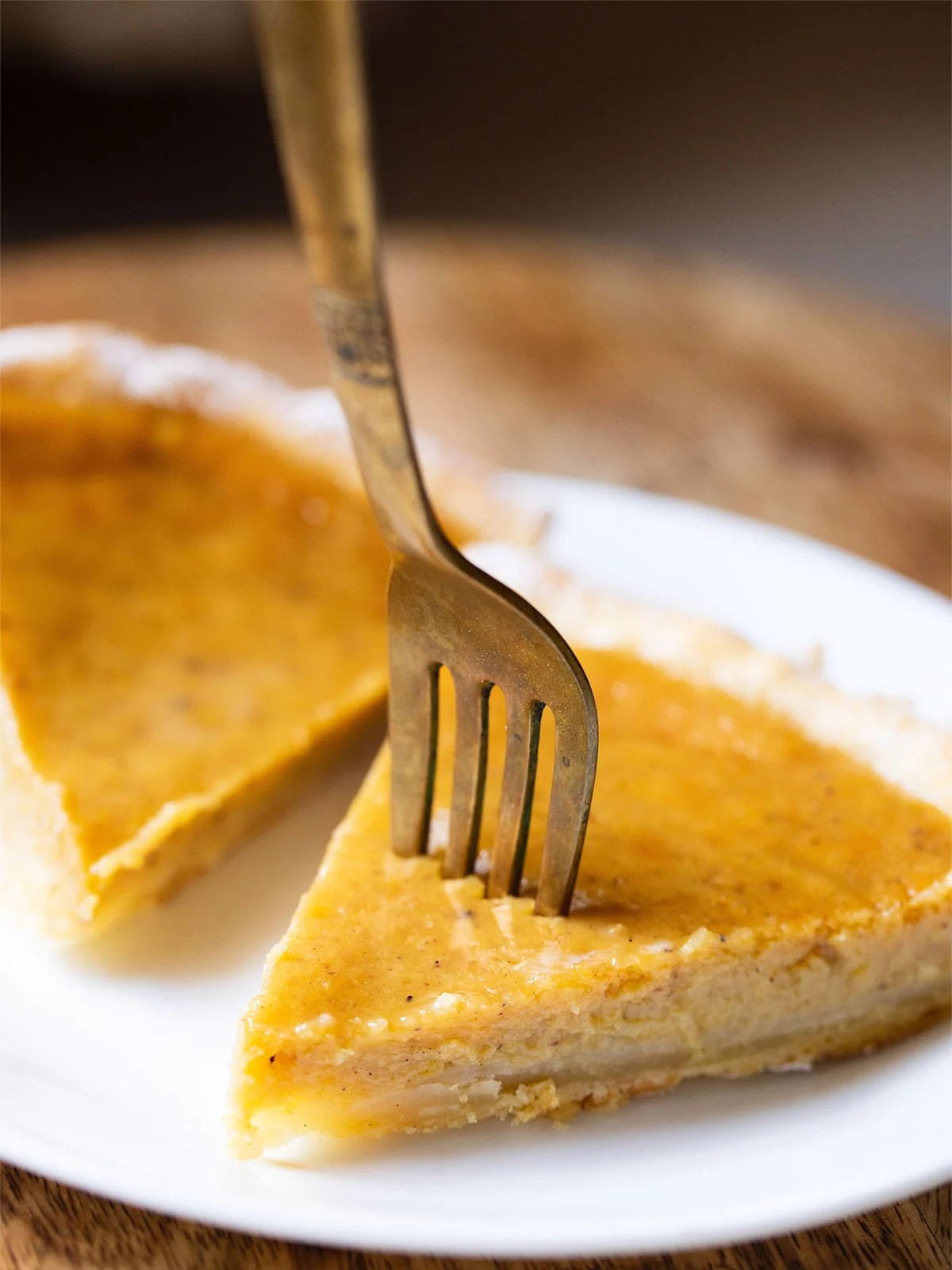 brass fork in a slice of easy eggless pumpkin pie