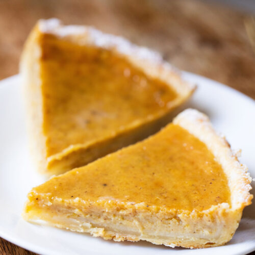 two pumpkin pie slices on a white plate