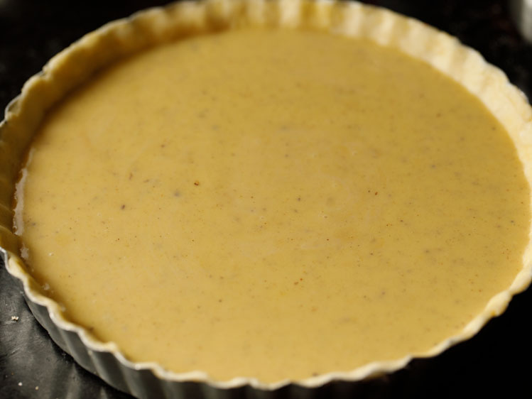 unbaked pumpkin pie in a silver fluted pie tin