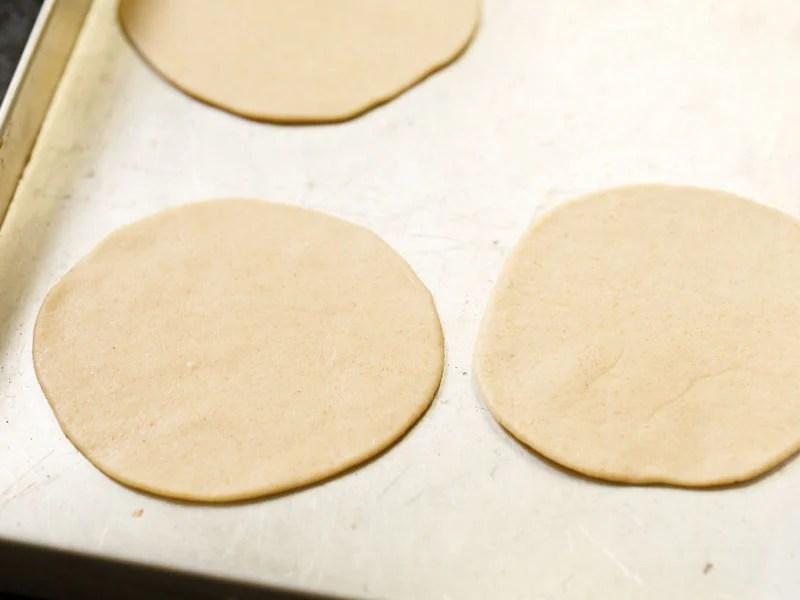 flat dough circles on a metal tray