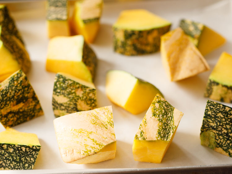 cubes of kabocha squash on a parchment lined baking sheet
