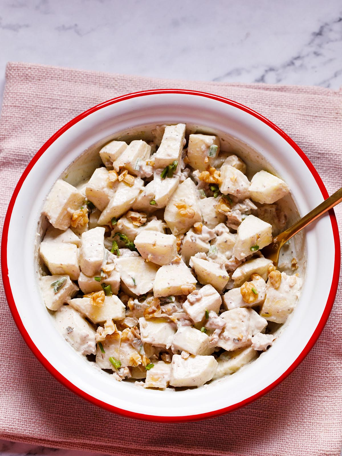 easy, creamy apple salad in a white and red ceramic bowl with a brass spoon a white background