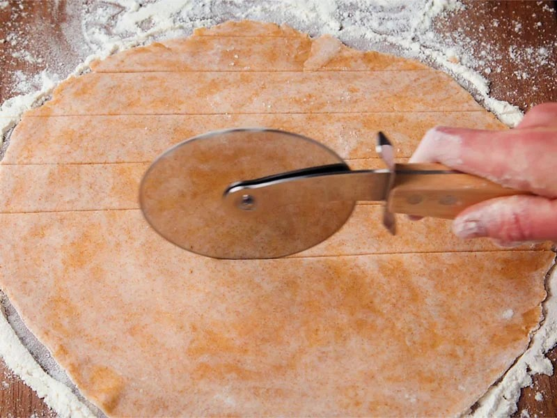 rolled vegan pie dough being cut with a pizza cutter