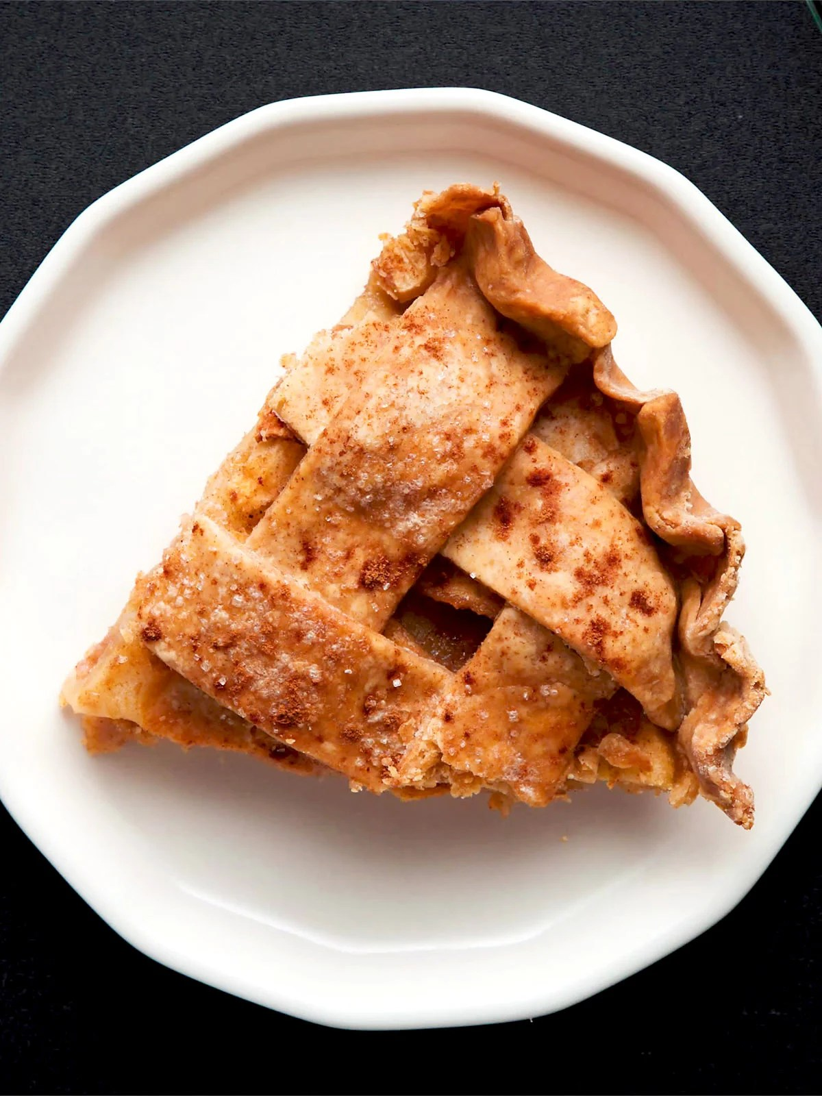 a triangular wedge of apple pie on an off-white plate