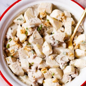 Apple salad with celery, walnuts and mayo dressing in an enamel bowl with white interior and red exterior with a brass spoon