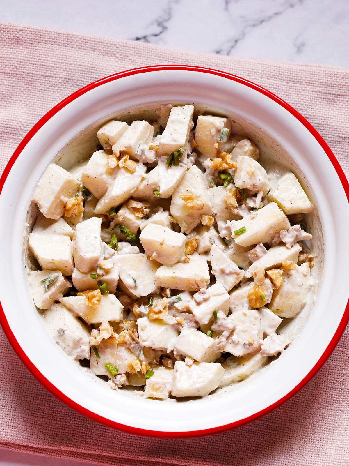 Apple salad with walnuts, celery and mayo dressing in an enamel bowl with white interior and red exterior