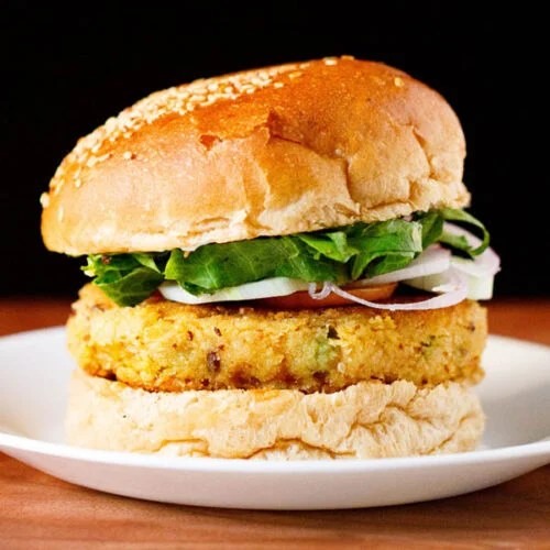 burger made with veggie patty, topped with onion, cucumber and lettuce on a white plate