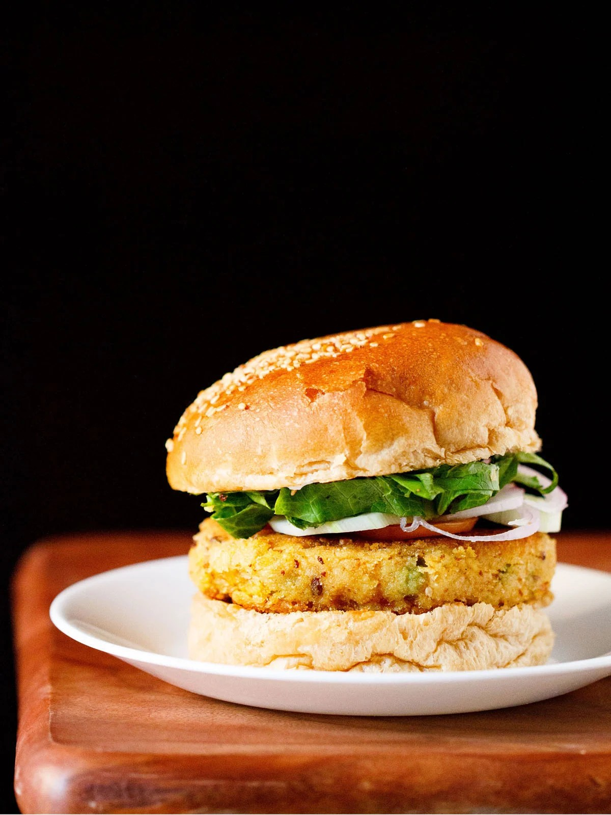 veggie burger on a white plate on wooden board with a black backdrop