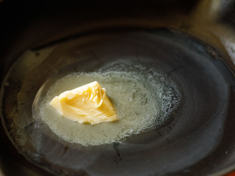 butter melting in a black skillet