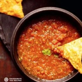 homemade salsa served in a black wooden bowl with a nacho chip dipped in the salsa