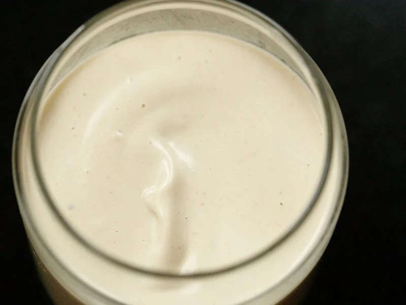 glass jar filled with vegan mayo on a black background