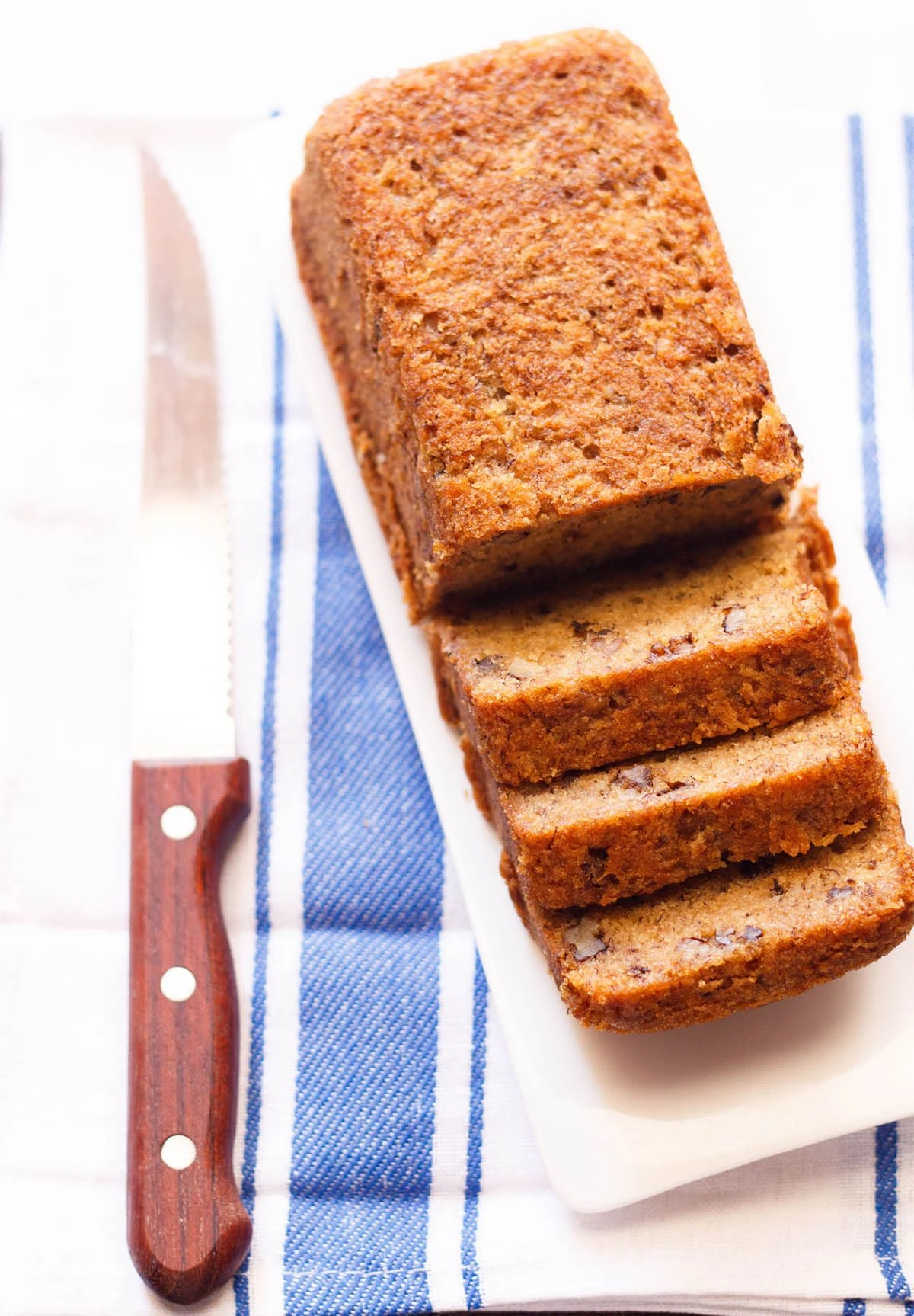 loaf of sliced eggless banana cake on white tray with serrated wooden knife on side