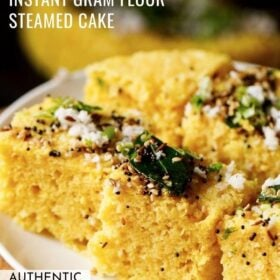 45 degree angle shot of khaman dhokla squares on a white plate garnished with cilantro, curry leaves and the fried curry leaves and spices mixture