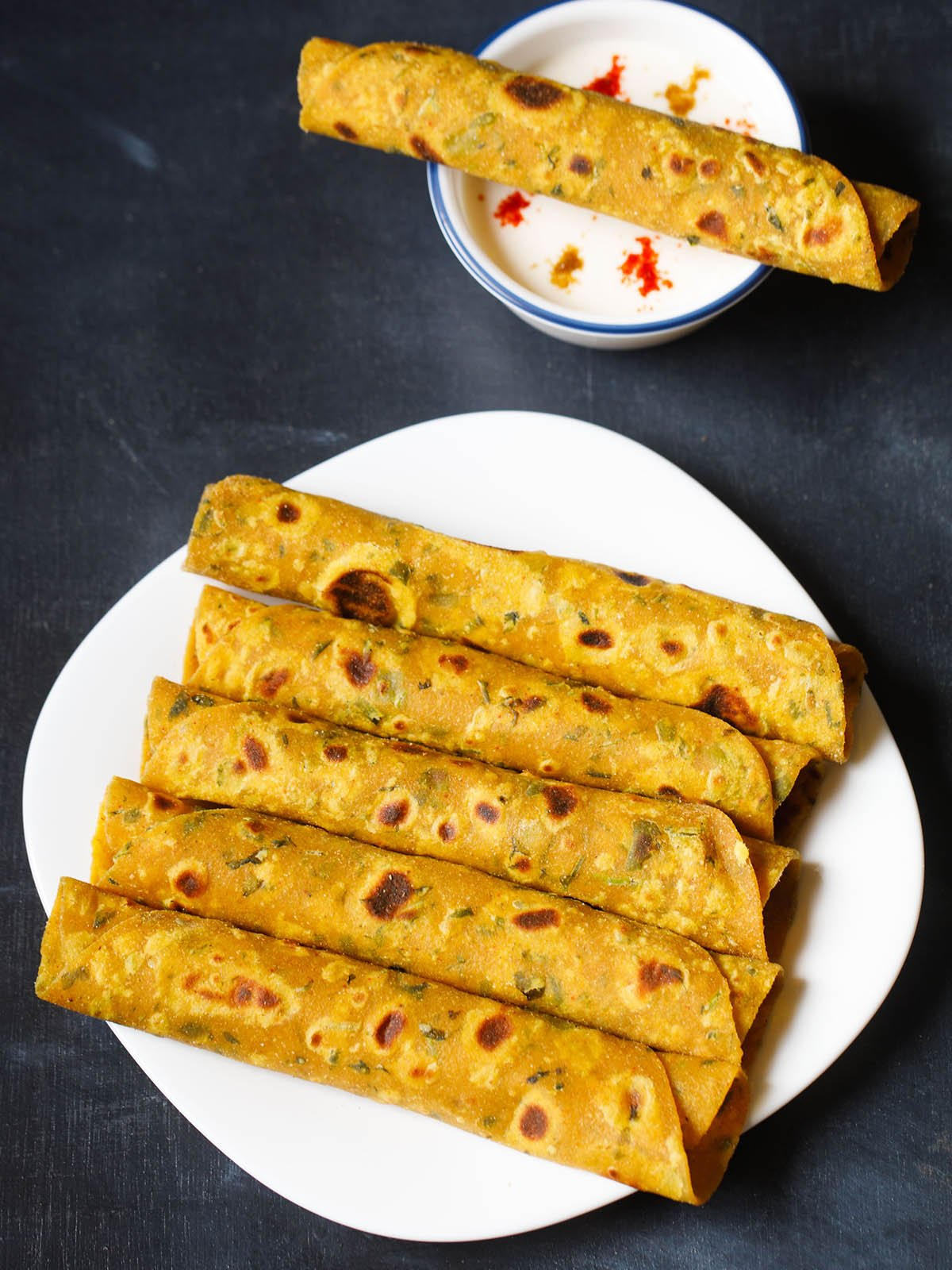 methi thepla rolls placed stacked vertically in white square plate on a dark blue black board