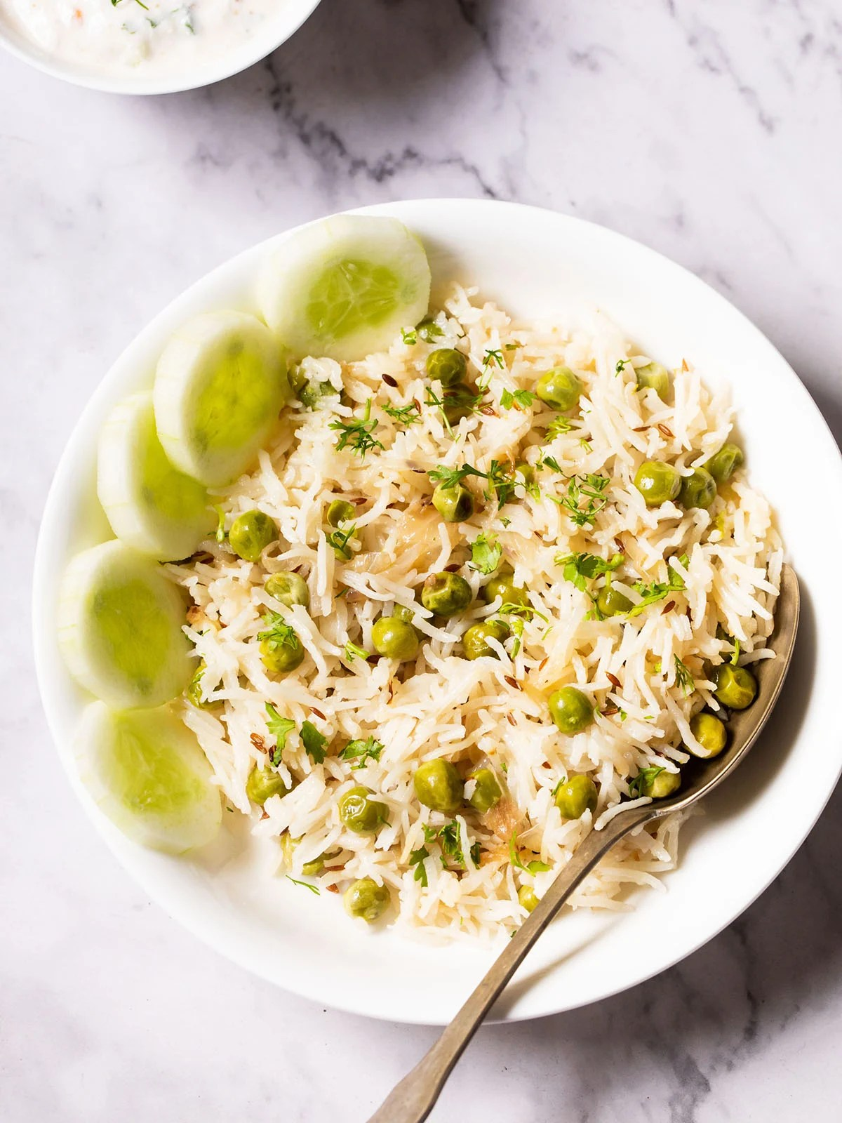 overhead shot of green peas pulao in a white shallow bowl with a brass spoon and cucumber slices placed at the left side on a white marble table