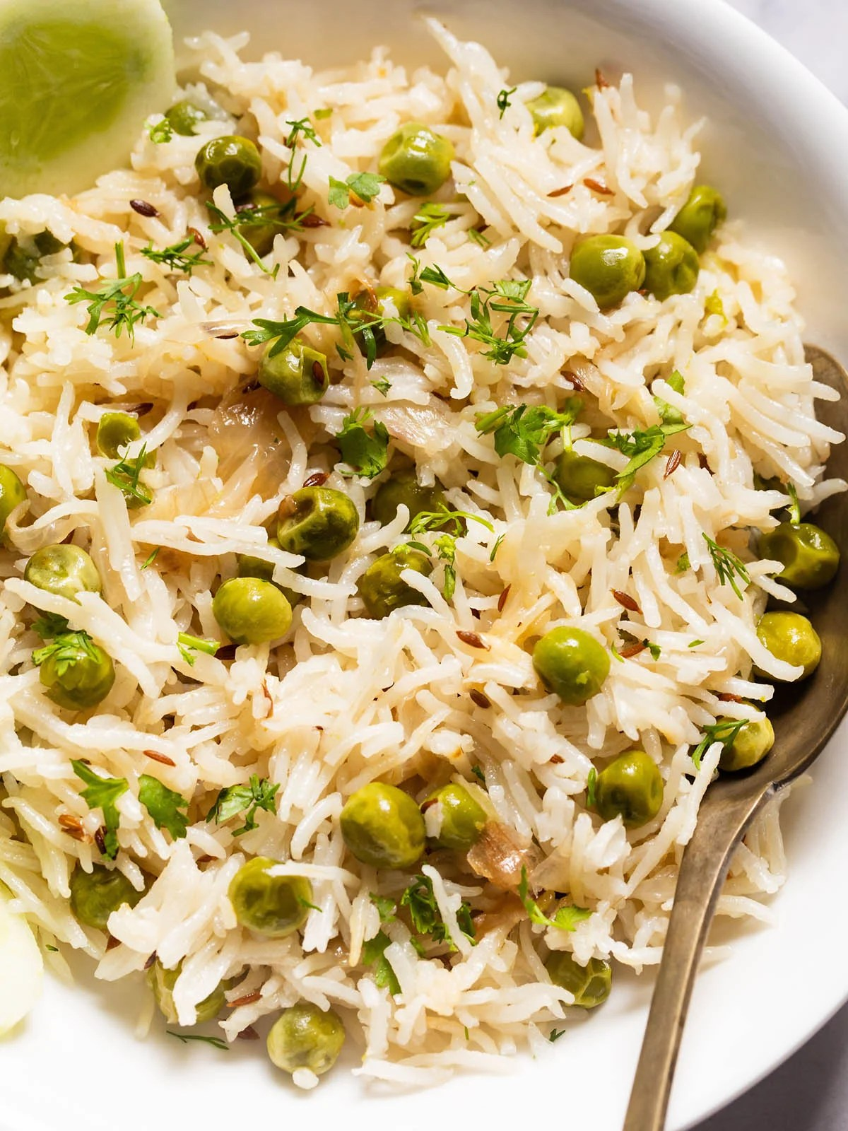 close up photo of peas pulao in a white shallow bowl with a brass spoon in the pulao