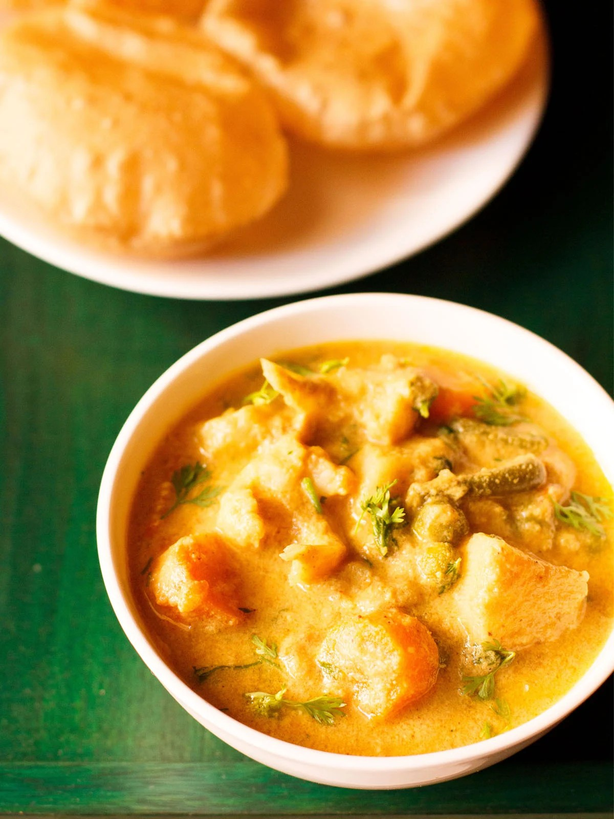 veg kurma in a white bowl on a dark green wooden tray with a side of poori