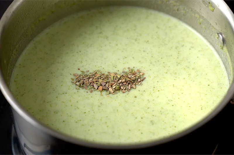 top shot of creamy broccoli soup with dried oregano added to the top in saucepan