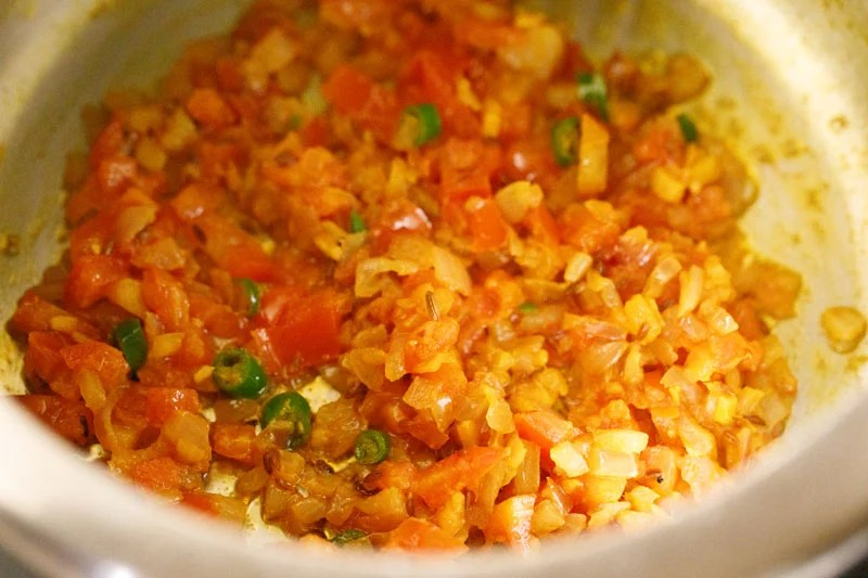 Top shot of sautéd tomatoes and khichdi ingredients in pressure cooker