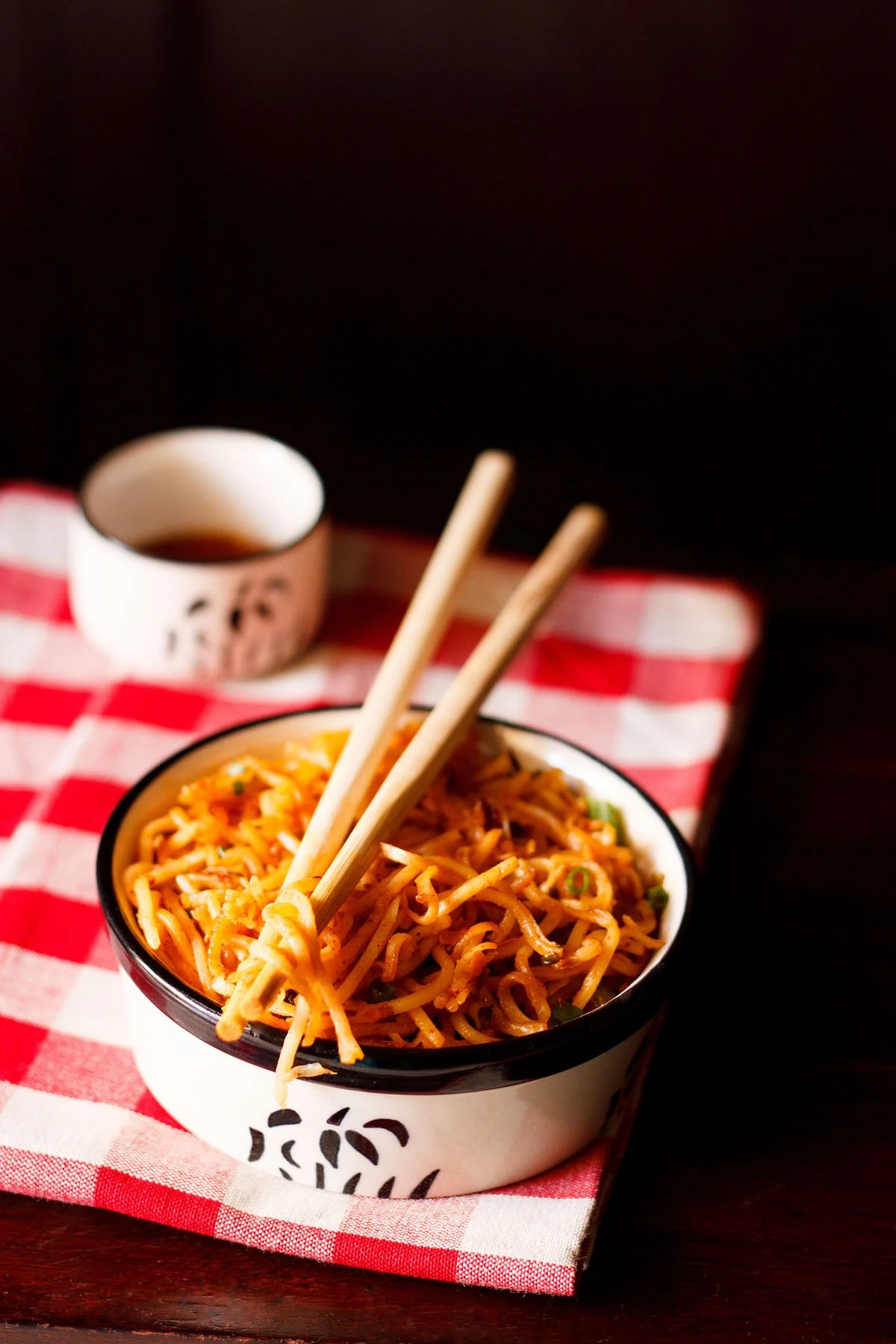 schezwan noodles in a black and cream bowl with a few noodle strands held between bamboo chopsticks placed on top of bowl on a checkered red and white napkin