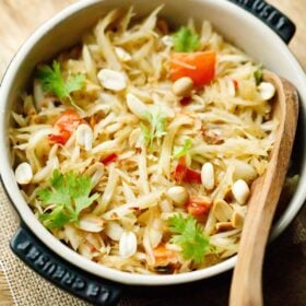 thai green papaya salad garnished with fresh cilantro and roasted peanuts in a black le creuset dish with a wooden spoon