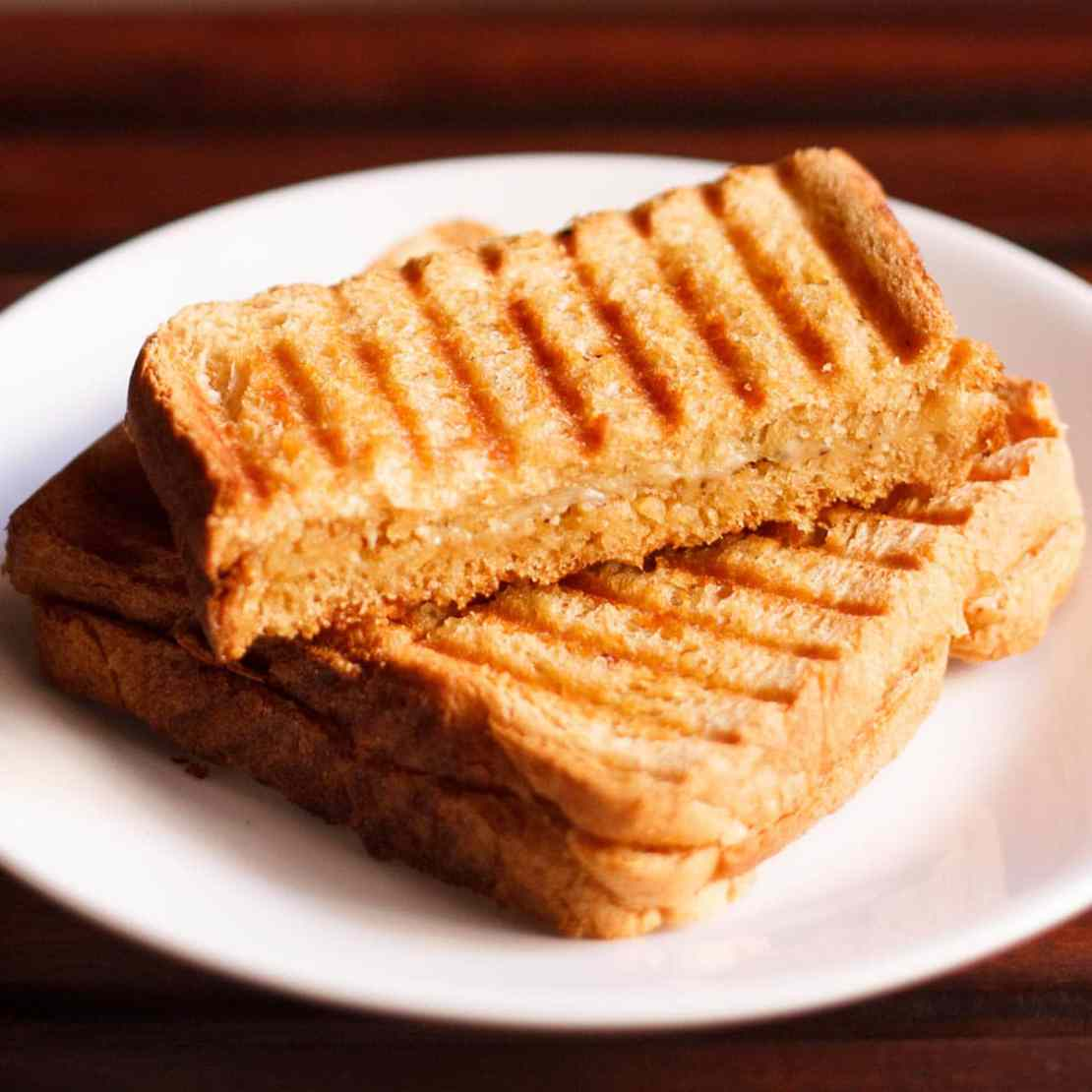 cheese sandwiches on a white plate on a dark brown table