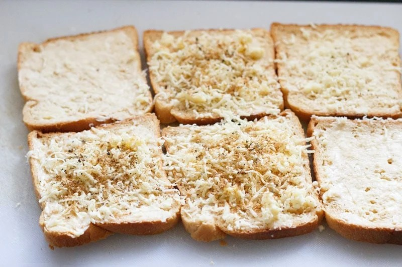 cheese on top of the buttered bread slices topped with ground spices