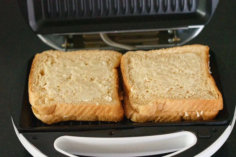 two cheese sandwich placed in a grill with butter spread on top of the bread