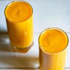 mango milkshake in two tall glasses on a white table