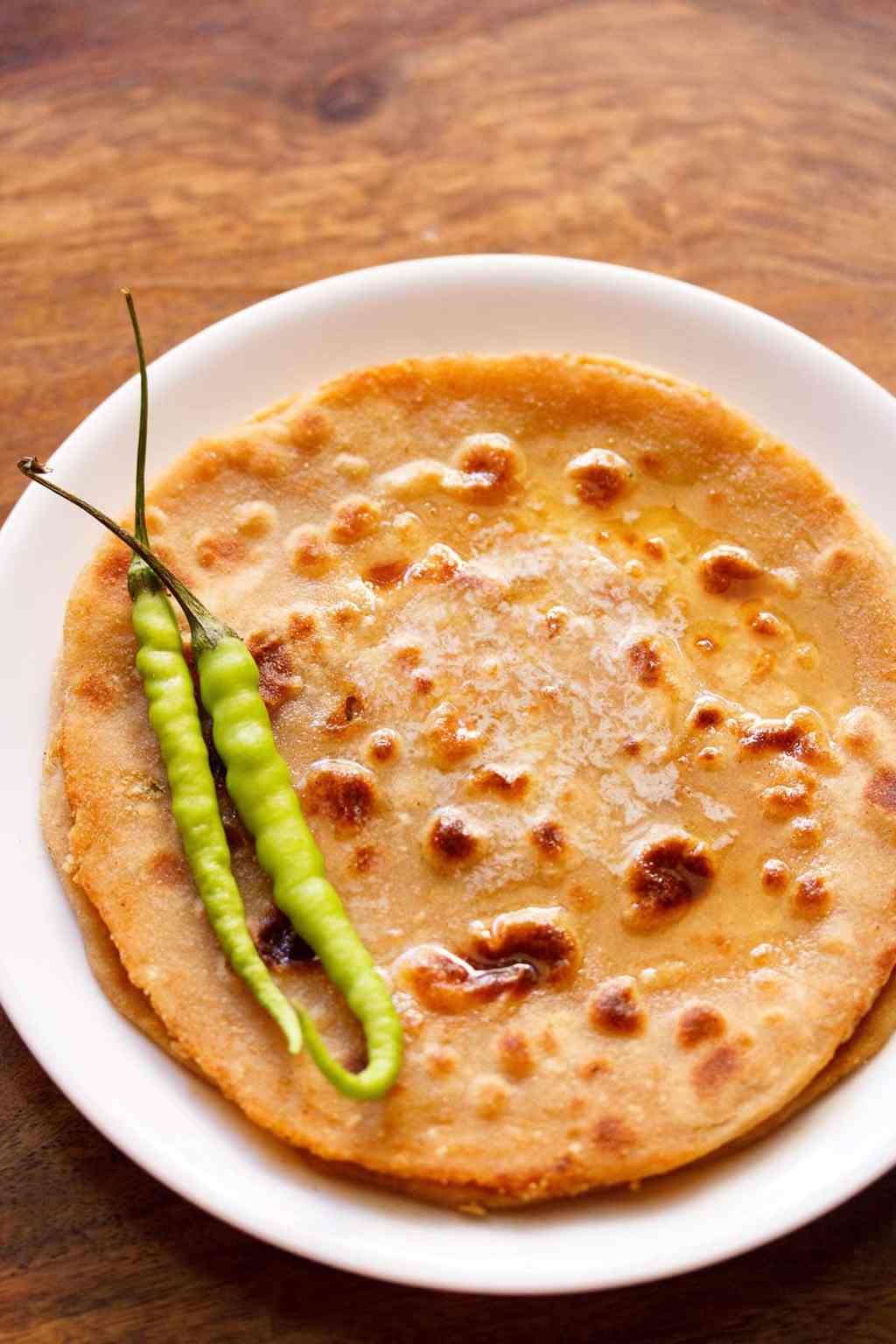 overhead shot of gobi paratha in a white plate topped with two green chillies at the side
