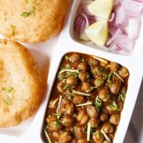closeup shot of white plate with sections filled with chana masala, sliced onions, fresh lime wedges and bhatura on a marble table-top