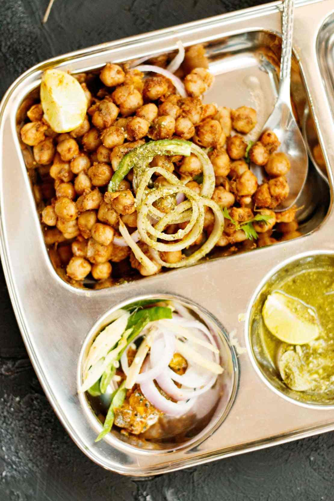 pindi chole served in a partitioned square tray with onion slices and lemon wedge on top with other partitions filled with onions, green chillies, mango pickle, lemon wedge and green chutney